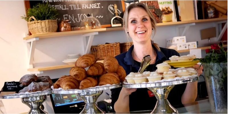 Barista holding a tray of cakes in cafe