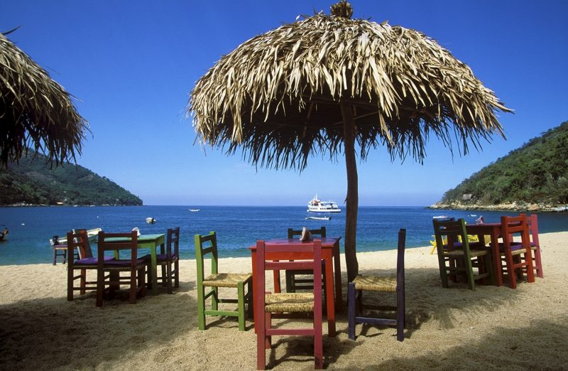 Bay and beach with wooden tables and chairs beneath thatched umbrellas