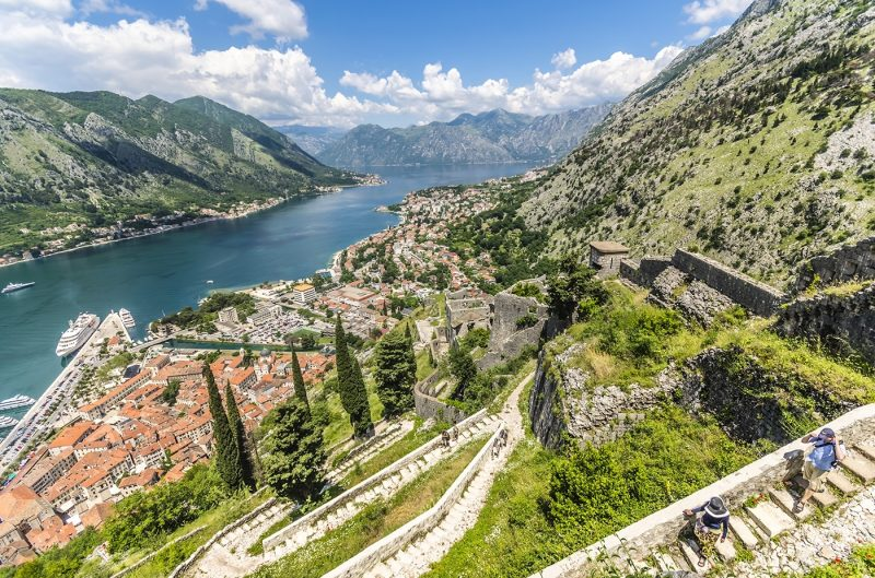 Hikers walking the old city walls during the daytime above the Bay of Kotor