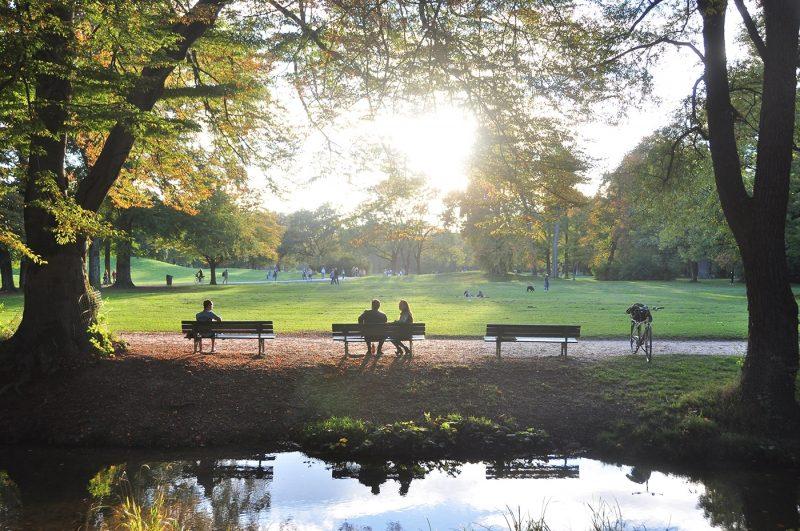 Couple sat on bench in Munich's English Garden