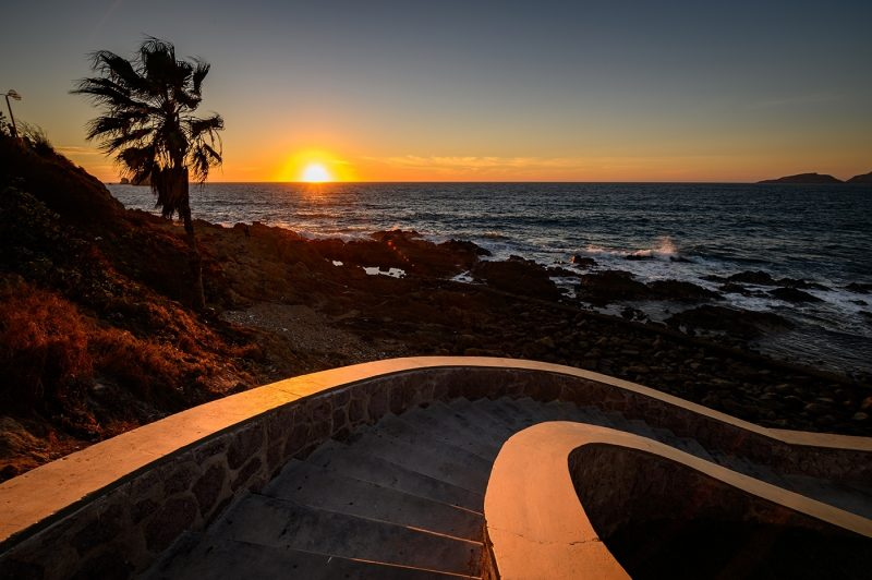 A curved stairway going down to Olas Altas beach at sunset in Mazatlan