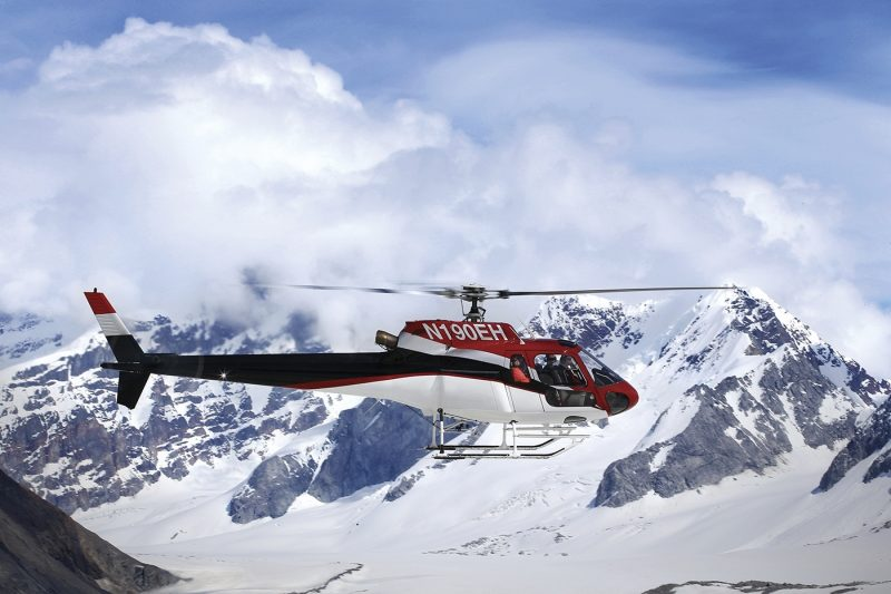 Red helicopter flying over mountains and glaciers