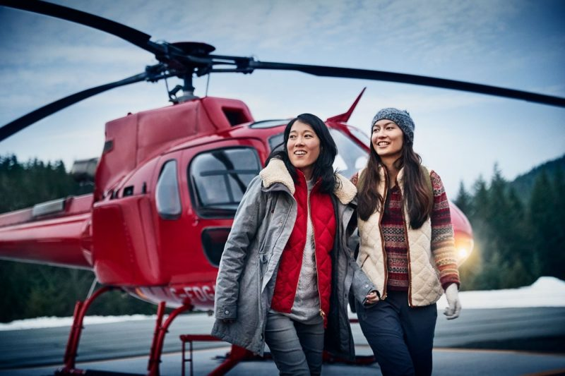 Two women in front of a helicopter as part of a Princess Cruises Alaska excursion