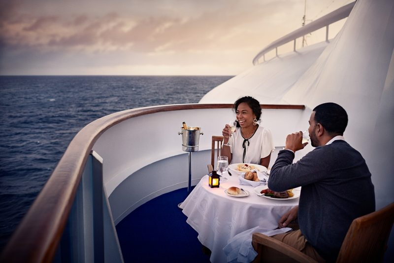 Two people dining at dusk on ship