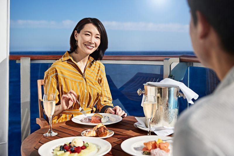A couple eating food on balcony