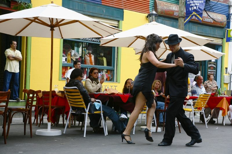 Couple dancing tango in the streets of La Boca outside a cafe
