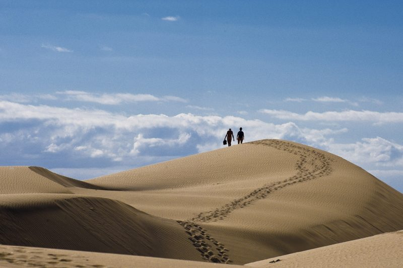 Two people on a sand dune