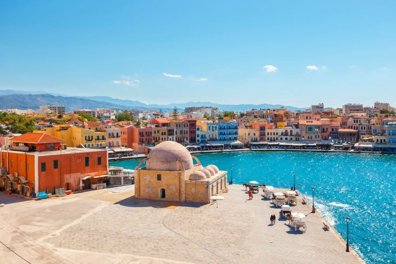 A view over buildings and bright turquoise water in Chania, Crete