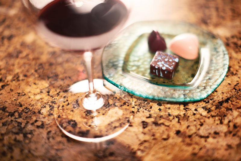 A glass of wine and a plate of chocolates