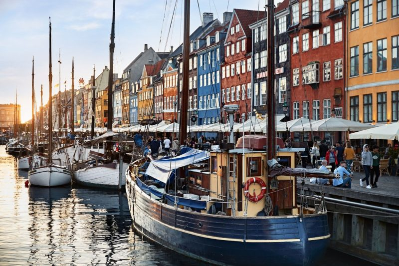 Boats on the water and colourful buildings along Nyhavn waterfront in Copenhagen