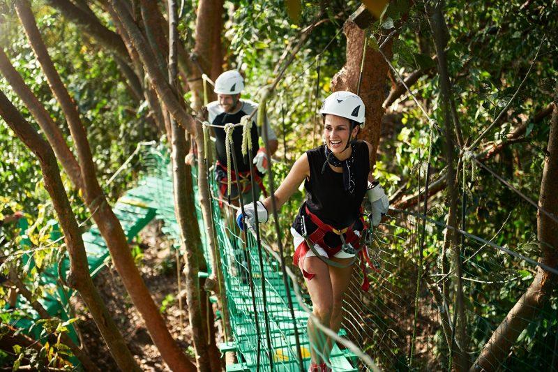 Two people ziplining in forest