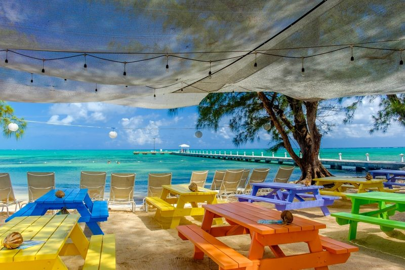 Coloured tables at beach bar on Rum Point at Grand Cayman