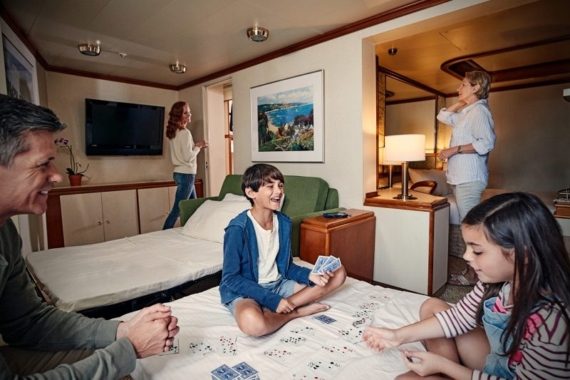 Family playing cards on a bed in a stateroom