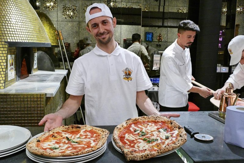Pizza chef making pizza with pizza oven in background