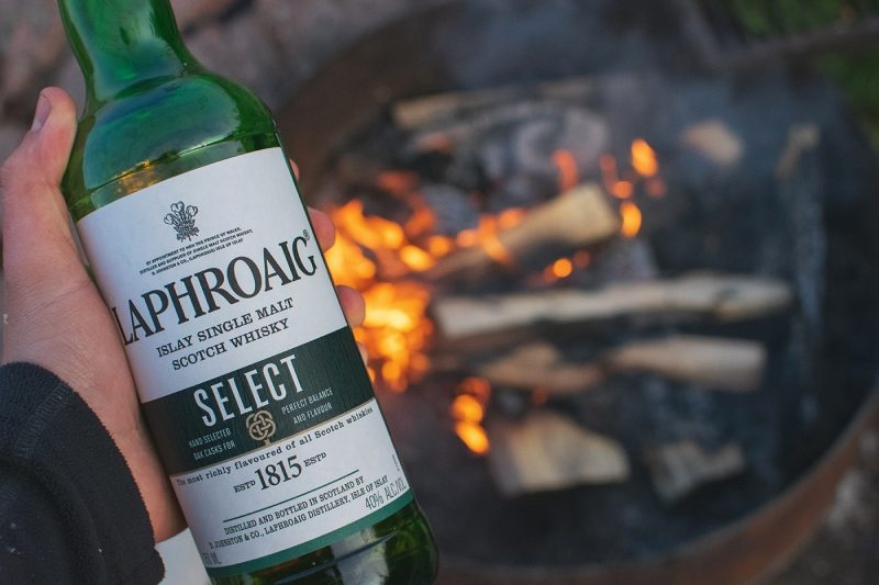 Man holding a bottle of Laphroaig whisky by a fire