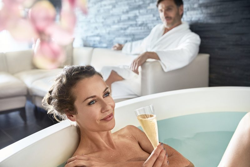 A woman relaxing in a spa with champagne