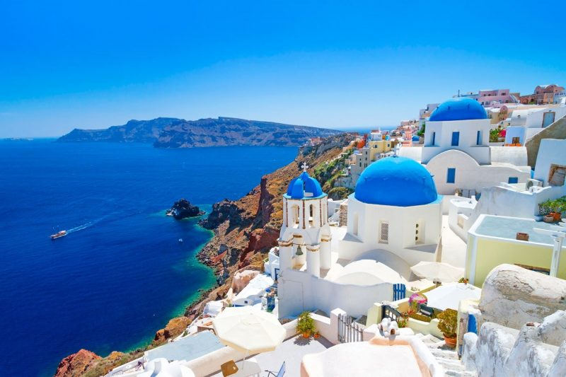 A view over blue seas with typical church buildings in the foreground in Santorini