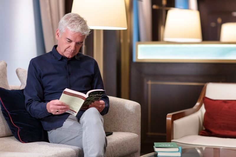 Phillip Schofield reading a book onboard Sky Princess