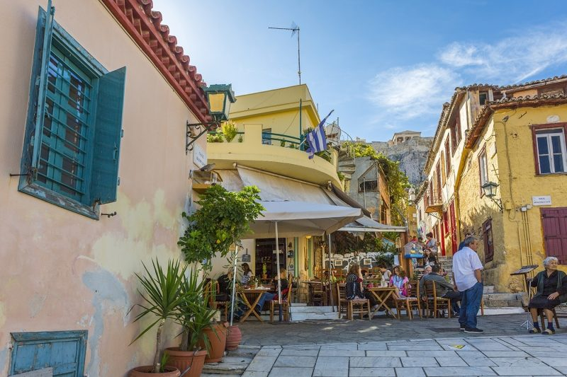 pastel coloured houses and cafe in Plaka District of Athens, overlooked by the Acropolis