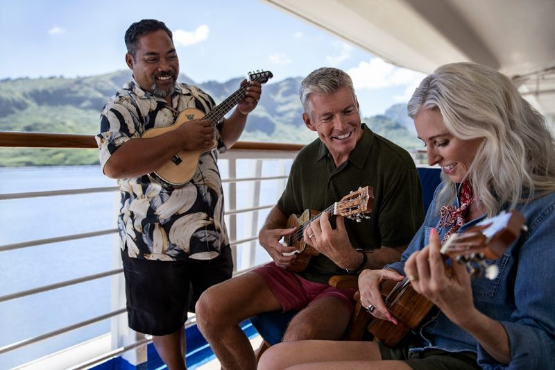 Couple playing ukelele onboard ship with instructor