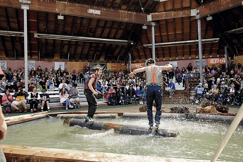 Two men taking part in log rolling in an Alaskan lumberjack show with Princess Cruises