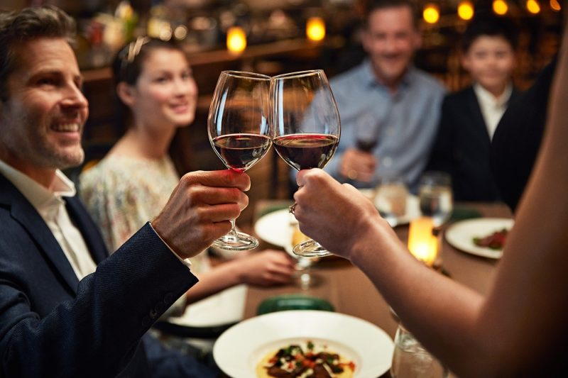 A group of people toasting with wine and pasta