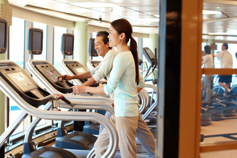 Couple using treadmill with screens