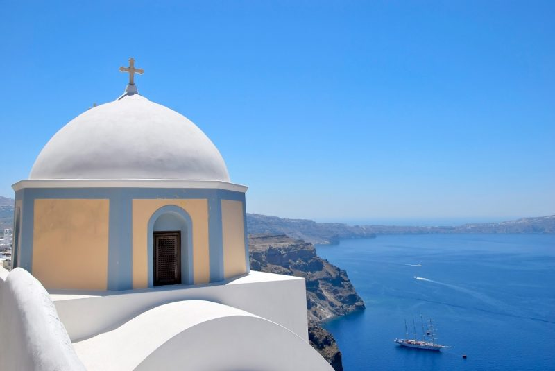 A traditional white domed church and blue sea in Santorini