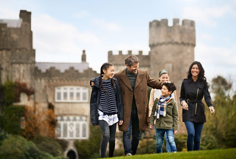 A family group walking in Dublin with a castle in the background