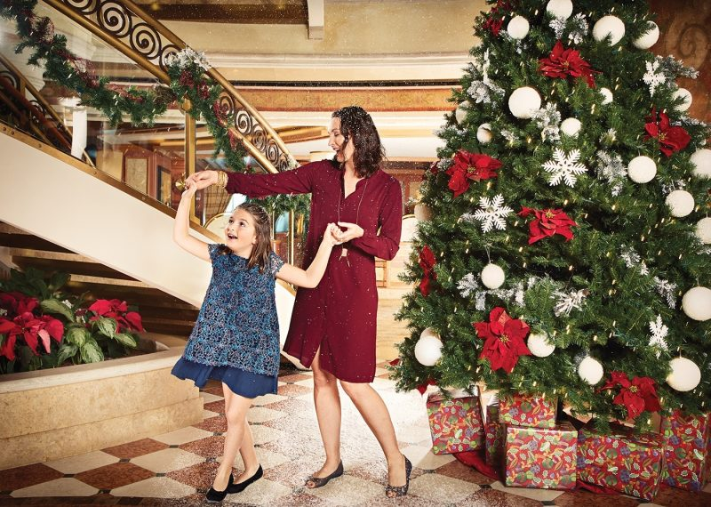 Mother and daughter dancing next to Christmas tree