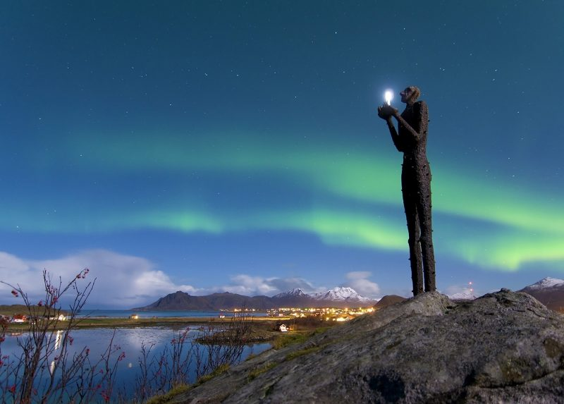 An outdoor sculpture holding a light, with northern lights in background