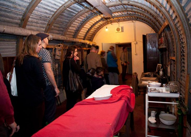 People walking through underground tunnels at Dover Castle that include a historic hospital mock up