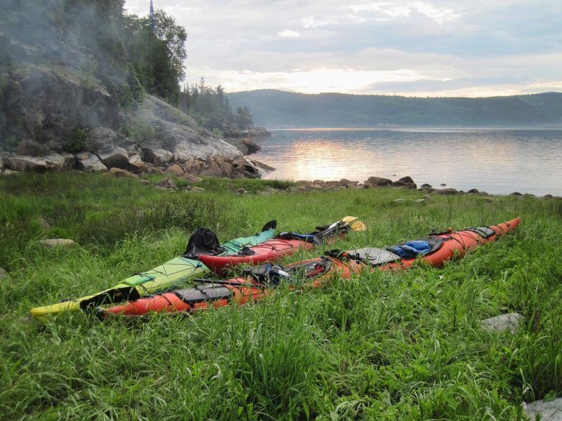 Two kayaks on grass by the sea in Saguenay, Canada