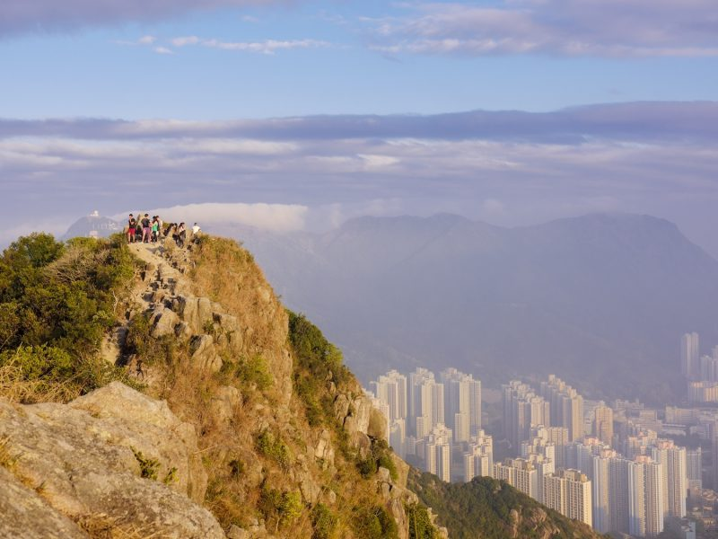 Hikers at the Lion Rock mountain peak, viewing the city of Hong Kong from a high point