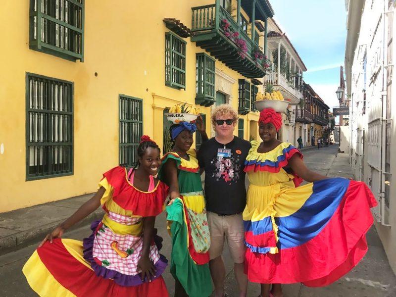 Jamie in Cartagena with brightly dressed dancers