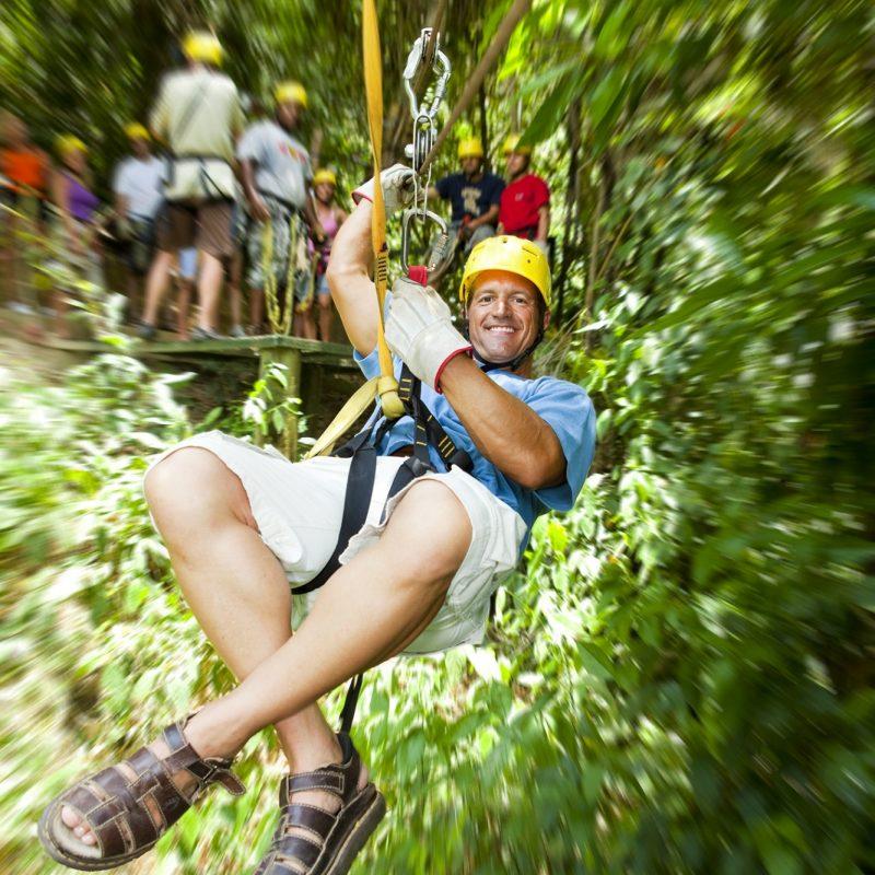 Man on a zipwire in trees in Honduras