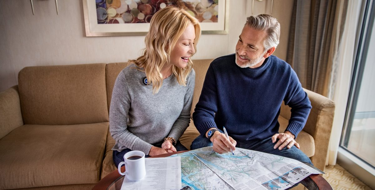 A couple with a map planning a cruise holiday