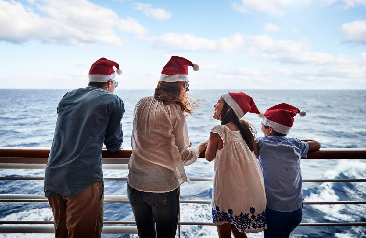 Family on deck of ship wearing santa hats