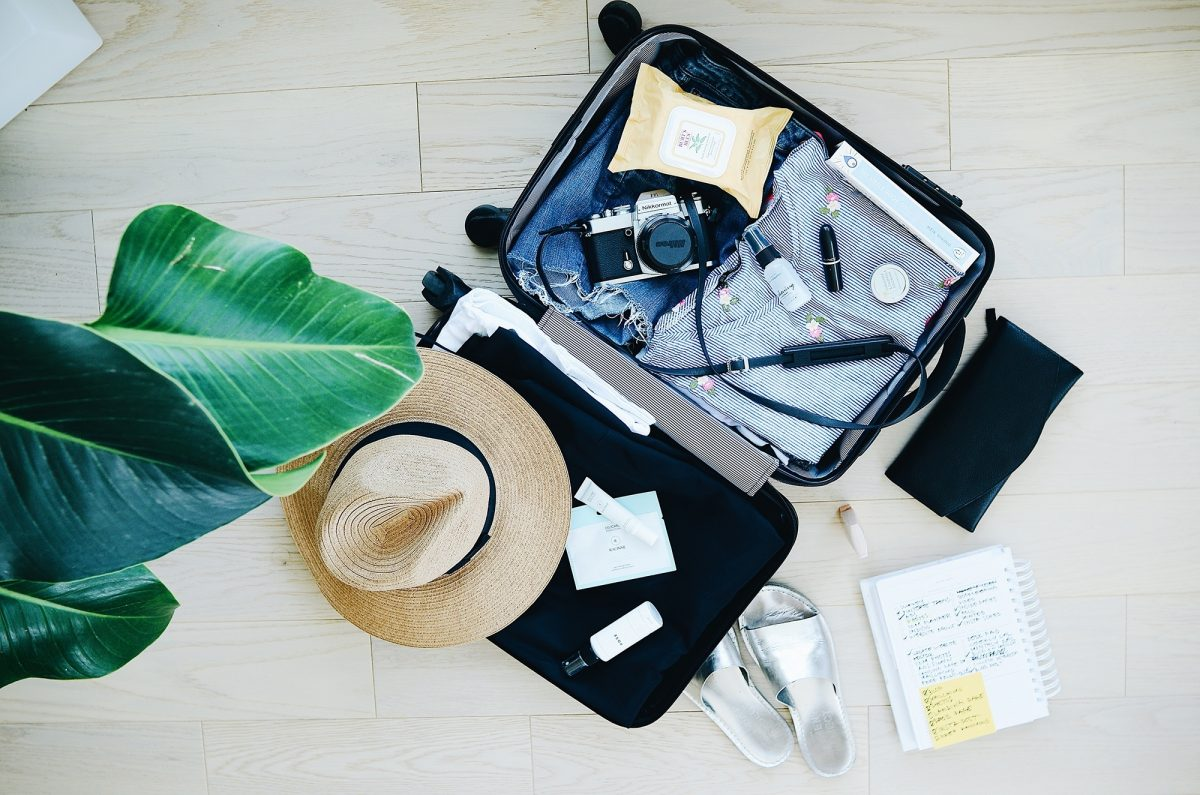 Open suitcase with holiday items
