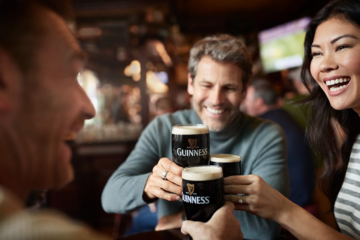 Three friends drinking Guiness in a pub in Dublin