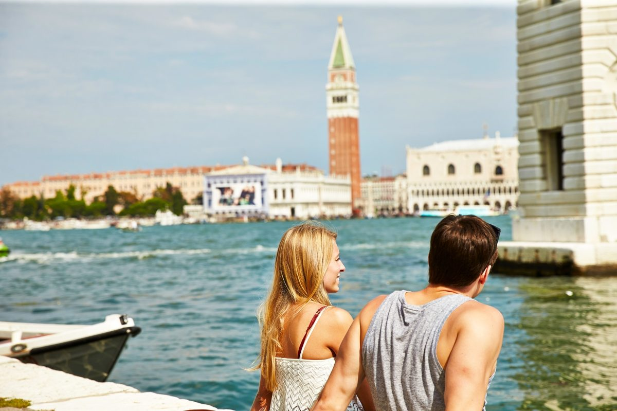 Two people sat by canal in Venice