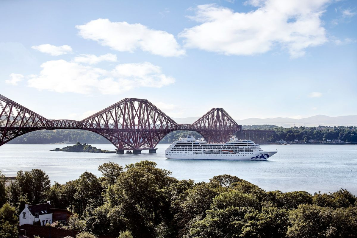 Pacific Princess sailing under the Forth Bridge in Scotland