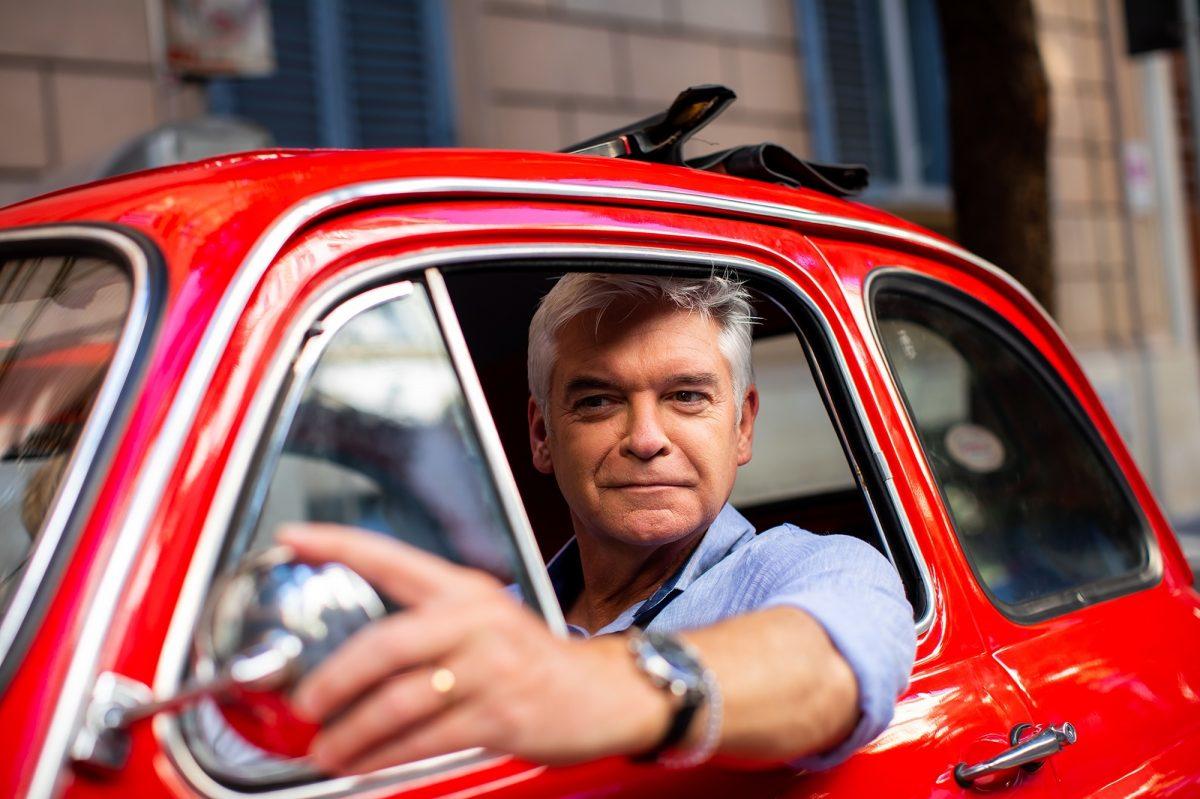 Phillip Schofiel driving a red Fiat car in Rome