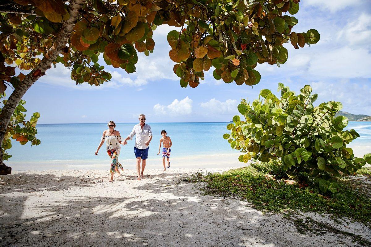 A family running on a Caribbean beach