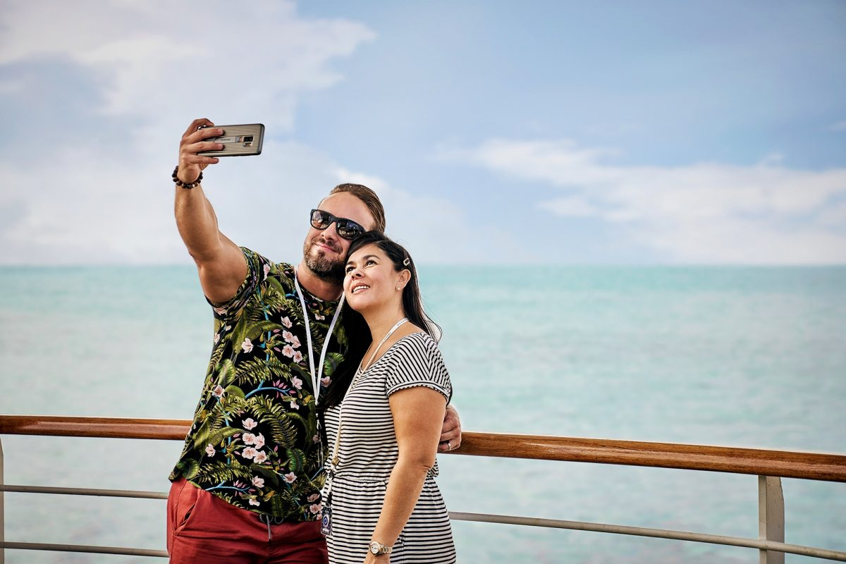 Couple taking photo with mobile phone on deck