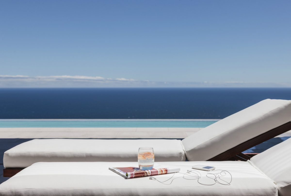 Phone and magazine on sunlounger in front of sea