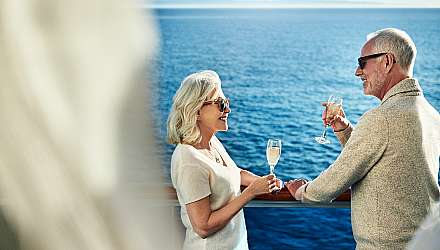 Couple toasting champagne on deck