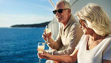 A couple enjoying a drink on their balcony onboard Princess