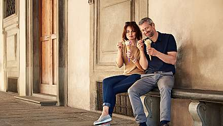 Couple eating ice cream sat on a bench