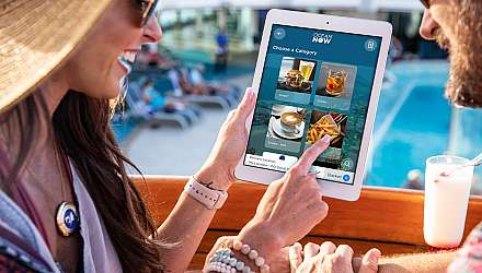 Two people using a tablet to order Ocean Medallion